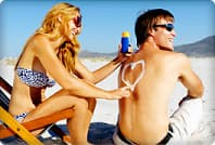 couple on beach applying sunscreen