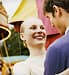 Teenage Couple standing in a fairground laughing 