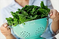 woman holding a colander of washed greens