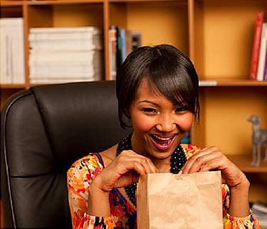 mixed race businesswoman opening paper bag at desk