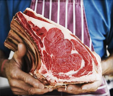 man holding joint of beef at market stall