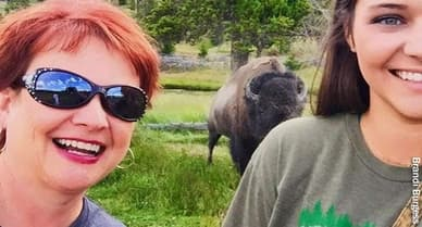 photo of women taking selfie with buffalo