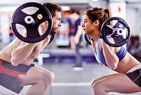 man and woman lifting weights