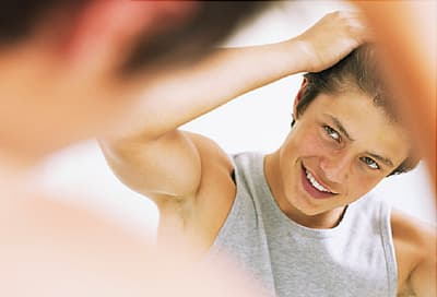 Teen boy combing hair