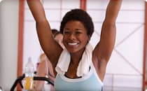 happy woman with arms raised in spin class