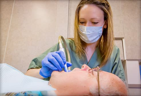 dental hygienist cleaning teeth