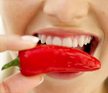 woman biting into red pepper