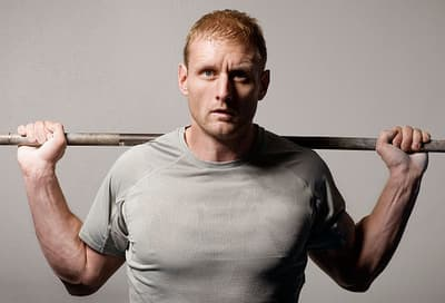 man lifting barbell behind shoulders
