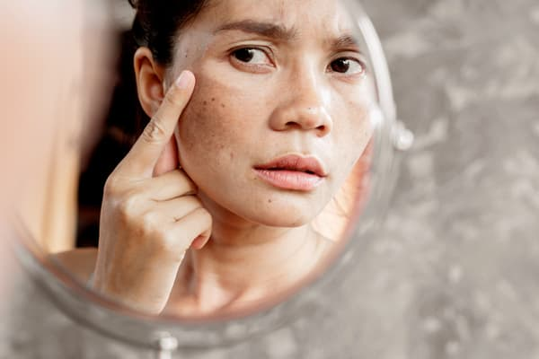 photo of woman looking in mirror
