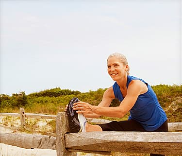 Mature woman stretching leg on fence