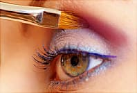 woman applying bright eye shadow