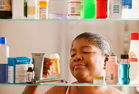 woman looking at bottle of pills