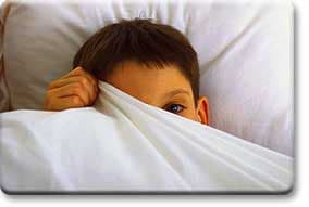 Tween boy hiding under bed covers