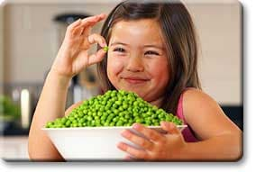Tween girl with bowl of green peas