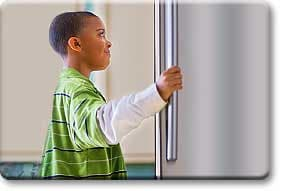 Tween boy looking into fridge