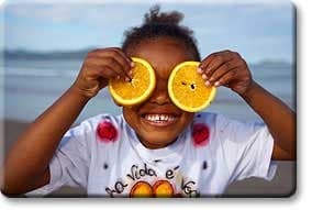 Tween holding oranges to eyes