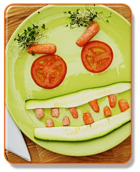 Face made of vegetables on plate