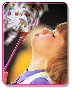 Girl blowing into pinwheel