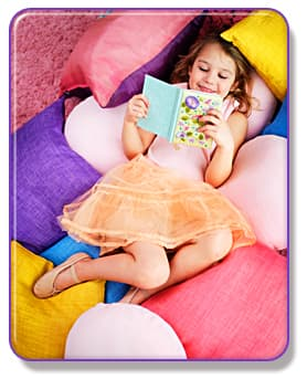 Girl reading on a pile of pillows