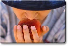 Tween biting into peach
