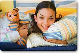 Tween lying on bed with pillow