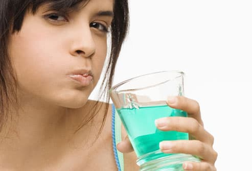 Young woman gargling with blue mouthwash