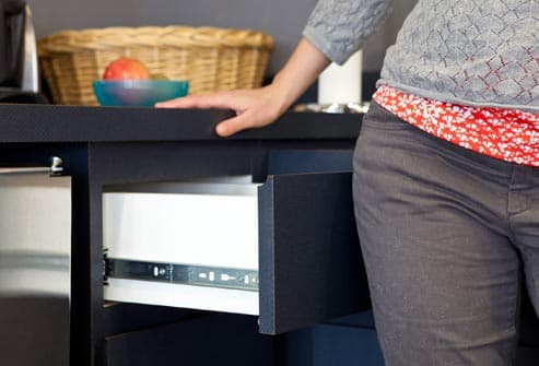 woman closing drawer with hip