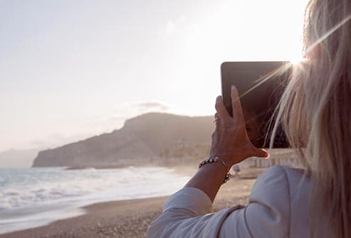woman taking picture of surf