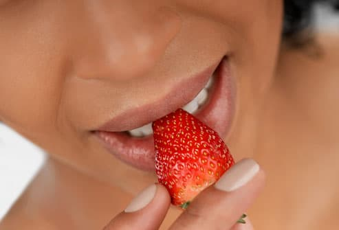 Woman Biting Into Strawberry
