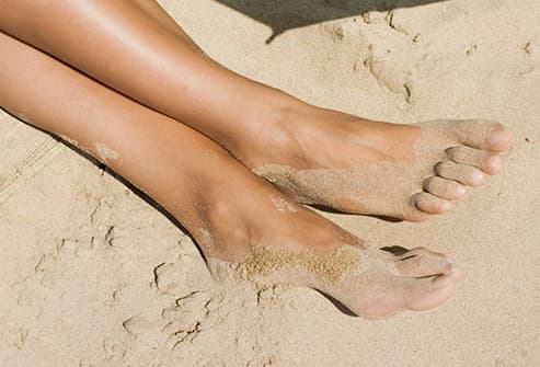 womans feet in sand