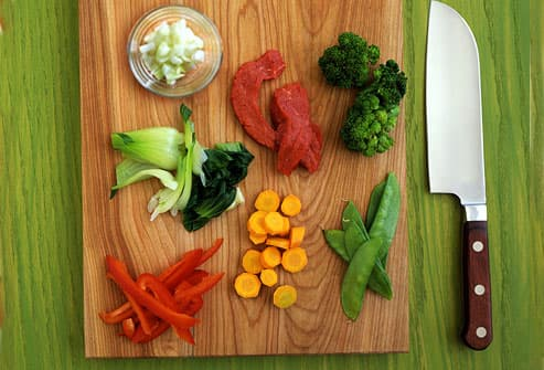 Cutting board with veggies and red meat
