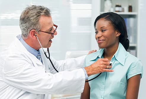 doctor listening to womans chest with stethoscope
