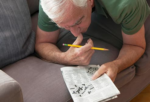 senior man working crossword puzzle