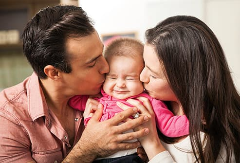 young couple kissing infant