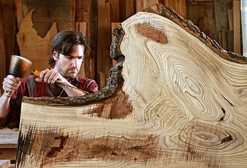 Carpenter chiseling a large section of a tree trun