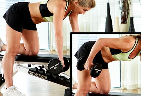 Trainer doing bent-over row with free weights