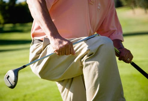 breaking golf club on knee