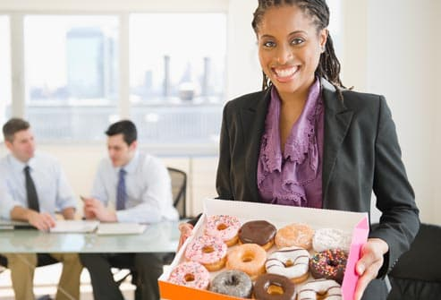 woman holding box of donuts