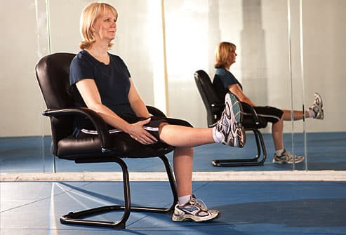 Woman in office chair stretching