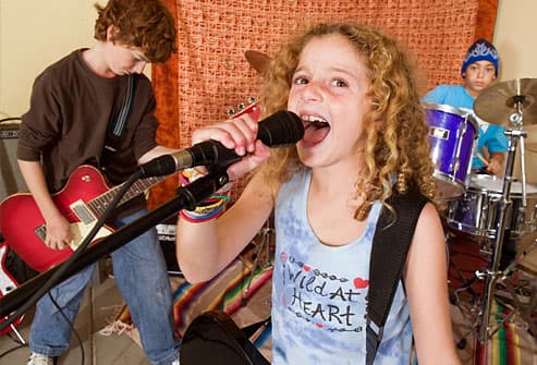 Getty rm photo of girl singing while friends play instruments