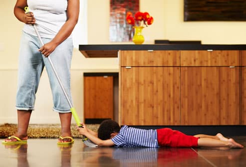 Mother sweeping while child hangs on broom