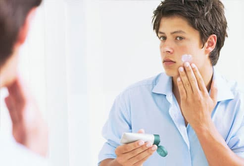 Young man applying cream to face