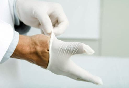 Photo of hands putting on latex gloves
