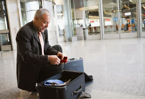 Man Packing Suitcase in Airport