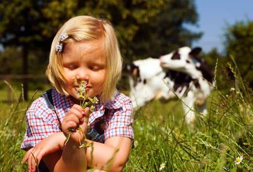 Young girl smelling flowers on a farm