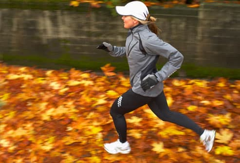 Woman jogging on sidewalk covered with wet leaves