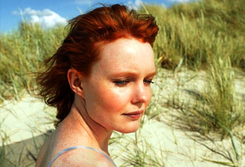 Woman surrounded by grassy beach dunes