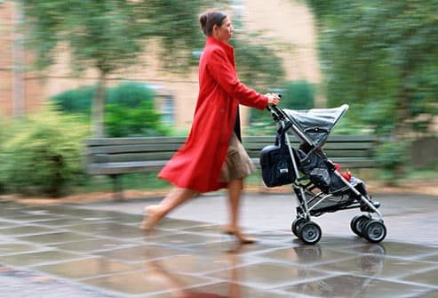 Woman with stroller crossing a rain soaked plaza