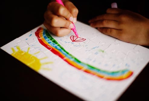 child drawing rainbow