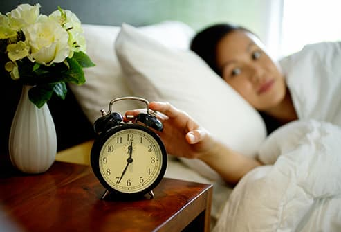 woman in bed reaching for clock